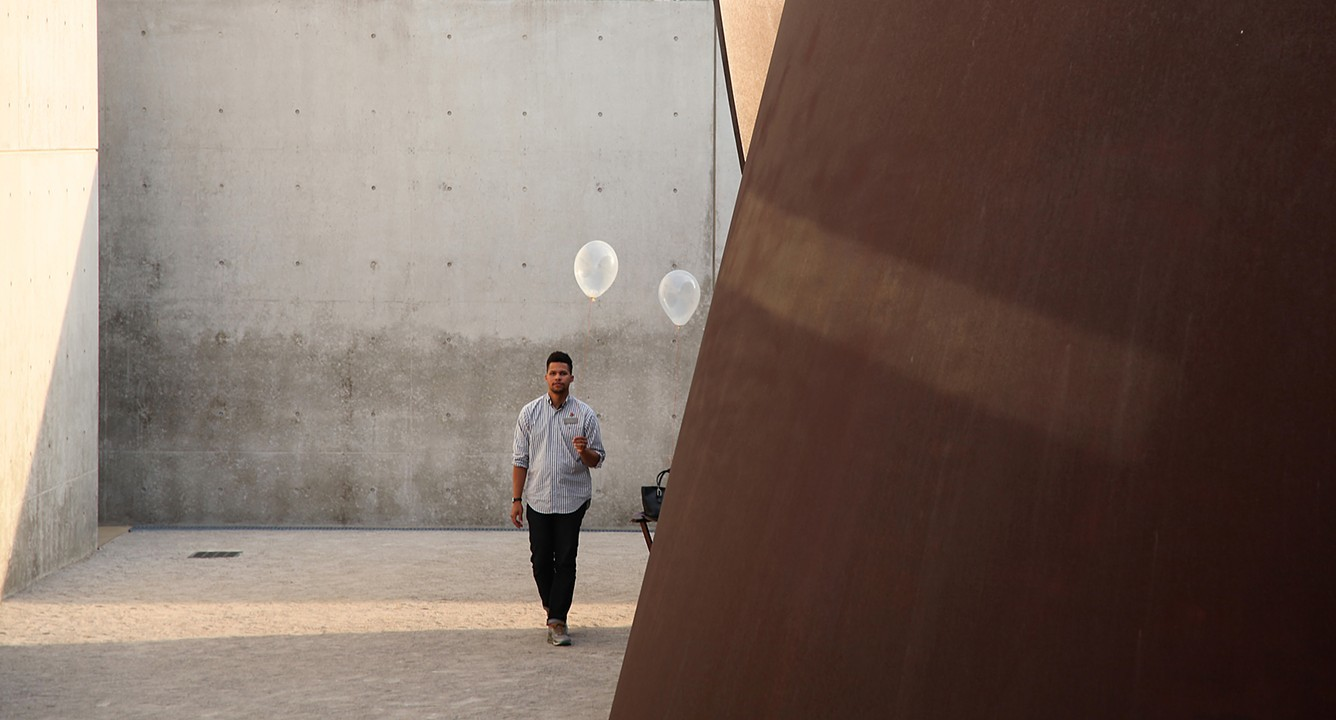 """A participant with a milkweed balloon stands next to """"Joe,"""" one of Richard Serra's torqued spirals."""